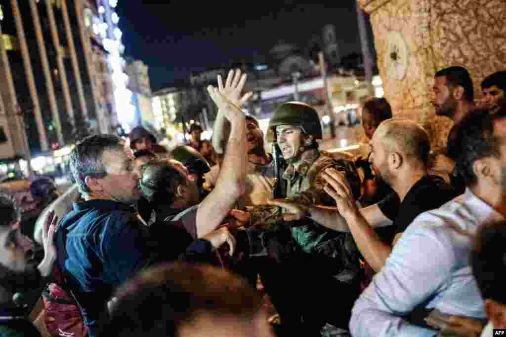 Turkey -- People react towards a Turkish solder at Taksim square in Istanbul on July 16, 2016.