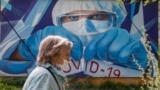 RUSSIA -- A woman wearing protective mask walks in front of a coronavirus graffiti showing a doctor with a face mask strangling with the coronavirus disease (COVID-19) pandemic on a wall in front of hospital in Krasnogorsk, Moscow region, May 15, 2020