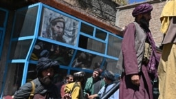 Taliban fighters stand beneath an image of legendary slain resistance fighter Ahmad Shah Masud in the Panjshir region's Bazark district on September 15, 2021, days after the hardline Islamist group announced the capture of the last province resisting their rule.