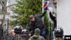 Депутат Владимир Парасюк прыгает через забор российского консульства во Львове сорванным российским флагом в руке