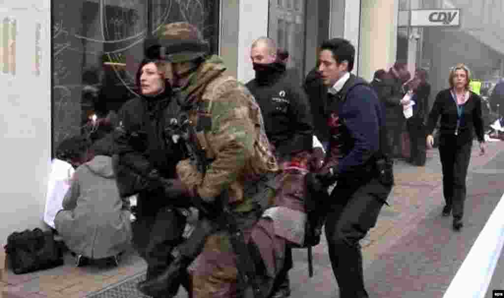 Бельгийские полицейские и солдат несут пострадавшего после взрыва на станции Маельбек