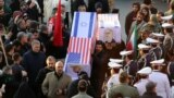 IRAN -- Mourners carry mock coffins with images of US President Donald Trump and Israeli Prime Minister Benjamin Netanyahu pasted on them as they gather to pay homage to slain Iranian military commander Qasem Soleimani, Iraqi paramilitary chief Abu Mahdi