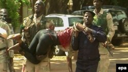Полиция выносит раненого заложника из отеля, захваченного террористами