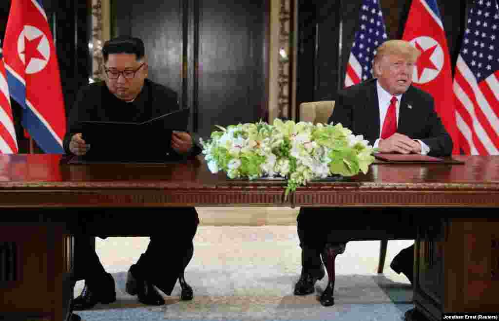 """Дональд Трамп комментирует подписание документа в то время, как Ким Чен Ын рассматривает только что подписанный документ.""""Сегодня у нас прошла историческая встреча, мы решили оставить прошлое позади. Мы решили подписать исторический документ – заявил северокорейский лидер Ким Чен Ын. – Мир увидит большое изменение""""."""