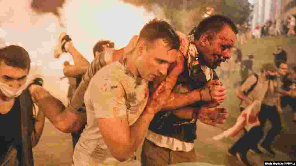 Демонстранты несут раненого Романа Зайцева, который сильно пострадал после взрыва светошумовой гранаты в ночь после голосования. 10 августа, Минск.