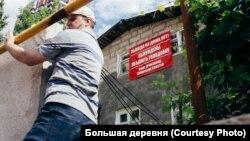 """Жилец забаррикадированного строителями дома карабкается через бетонные блоки, чтобы попасть на свой участок. Фото: """"Большая деревня"""""""