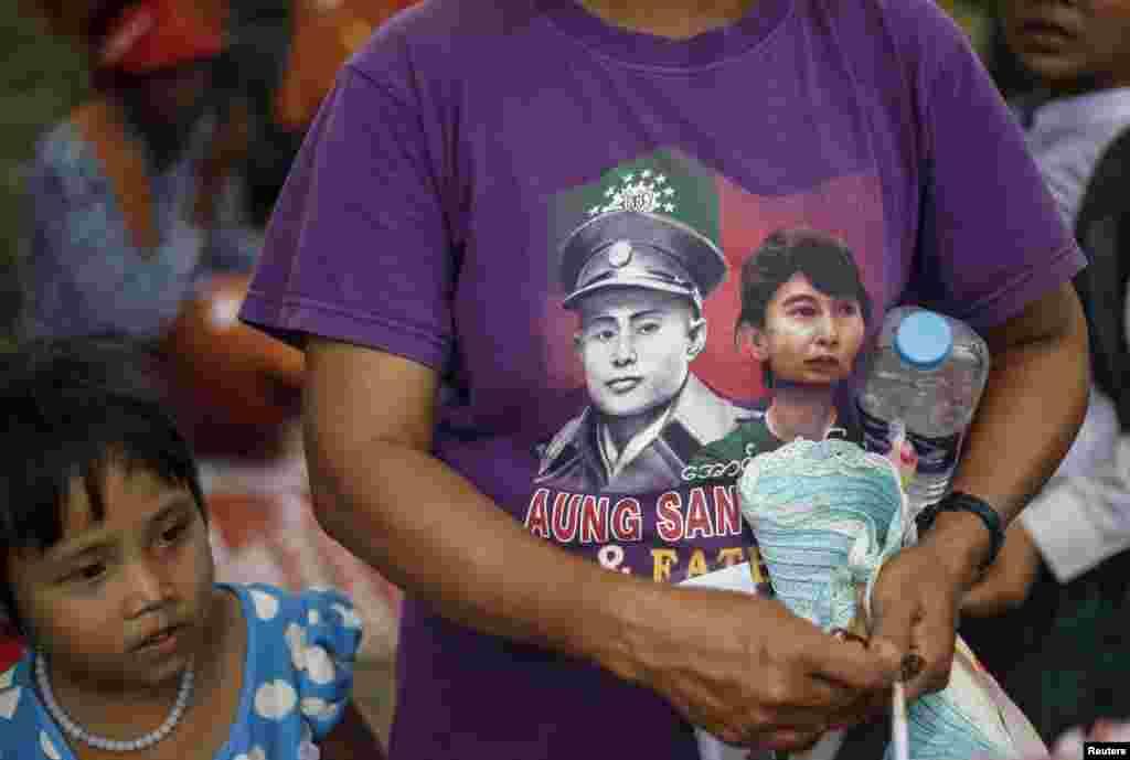 В Мьянме популярны футболки с изображением Аун Сан Су Чжи (справа) и ее отца - национального героя страны Аун Сана (слева). Су Чжи стала негласным символом в борьбе за демократию