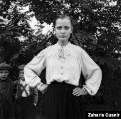 Девушка пронзительно смотрит в камеру на фоне детей