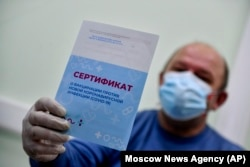A man shows his vaccination certificate after getting a shot of Russia's Sputnik V coronavirus vaccine in Moscow on December 28, 2020.