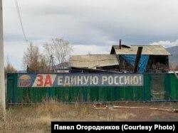Растяжка на фоне разваливающегося дома в поселке Усть-Омчуг