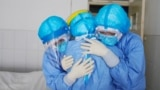 medical staff members hugging each other in an isolation ward at a hospital in Zouping in China's easter Shandong province