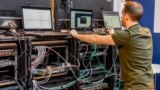 A man works next to servers specialised in cyber security