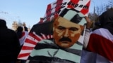 Minsk, Belarus - A demonstrator carries a placard depicting Belarusian President Alexander Lukashenko during an opposition rally to reject the presidential election results