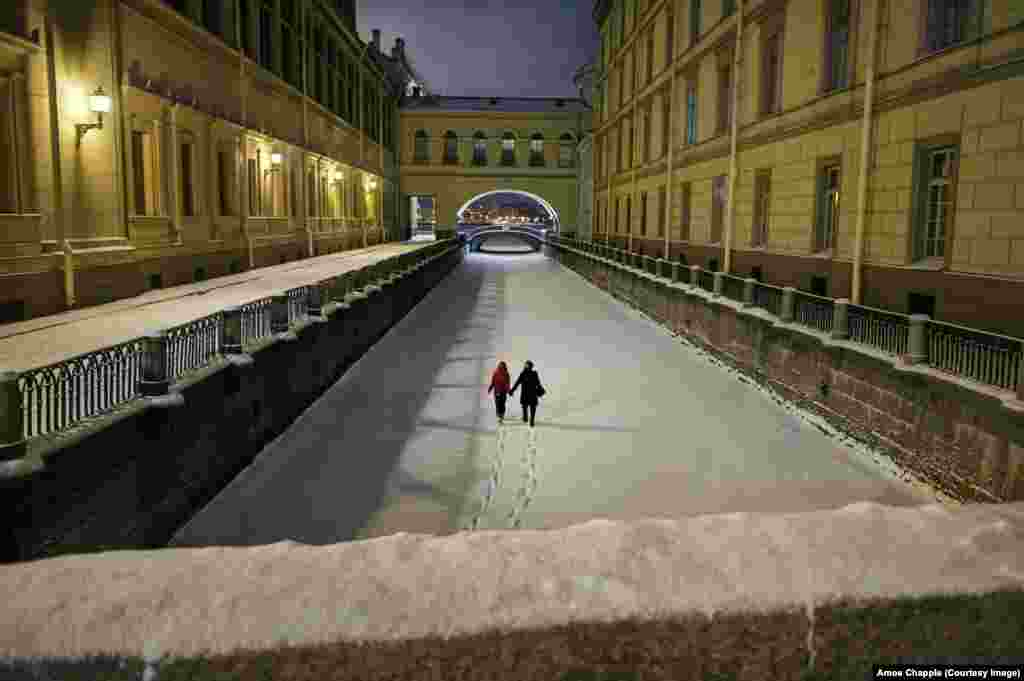 Пара идет по льду замерзшей Зимней Канавки после снегопада