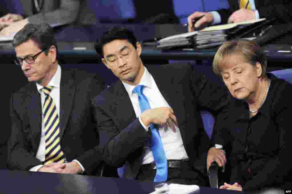 Канцлер Германии Ангела Меркель (справа), министр экономики Филипп Реслер (в центре) и бывший министр иностранных дел Гидо Вестервелле (слева) утомились на одном из заседаний в Бундестаге