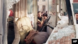 Baku residents on January 21, 1990 examine a bus caught in the attack by Soviet troops.
