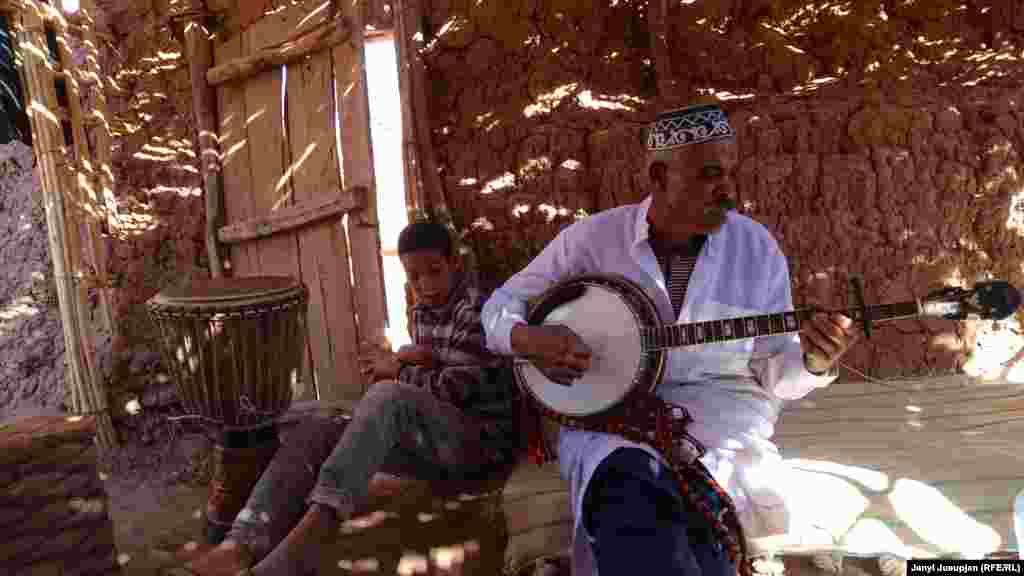 """Культура – один из главных столпов туризма в Марокко. Больше 60% туристов едут сюда посмотреть историческое наследие страны. На фото Aбделислам по прозвищу """"Мусташ"""" (Усы) с сыном в летнем шалаше. """"Мусташ"""" устраивает для туристов выезды на природу с обедом. После поездки они с друзьями играют марокканские мелодии и танцуют"""