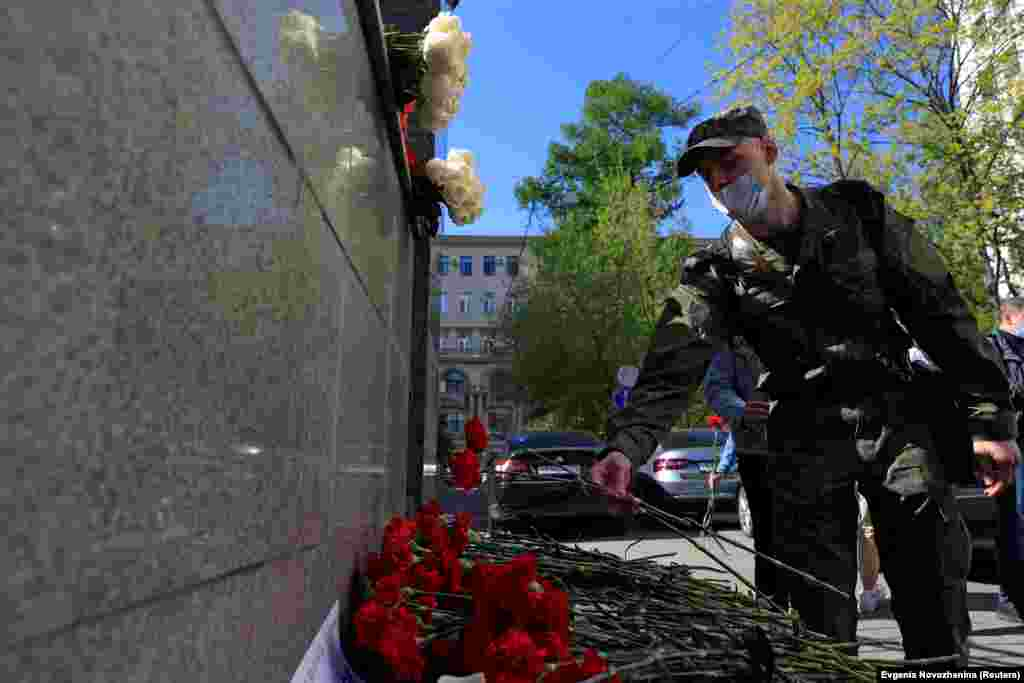 A serviceman lays flowers at a makeshift memorial outside the Republic of Tatarstan's office in Moscow to commemorate victims of the May 11, 2021 shooting at Kazan's School No. 175.