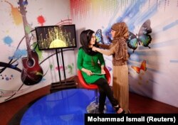 Khatira Ahmadi, a producer at Kabul's all-women Zan TV station, adjusts the headscarf of a presenter before recording on May 8, 2017.