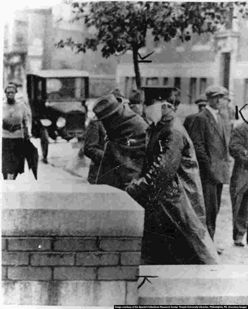 Полицейский сопровождает больного испанкой в больницу в Филадельфии, октябрь 1918 года