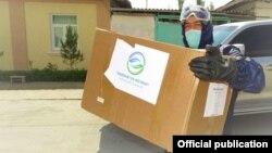 """Волонтер с коробкой фонда """"Доброта и поддержка"""" (""""Саховат ва кўмак"""")"""