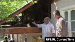 Komil Muminov shows Current Time Asia correspondent Anushervon Aripov damage to the roof of his house in the Tajik village of Somoniyon, following the April 28-April 29, 2021 fighting with Kyrgyzstan.