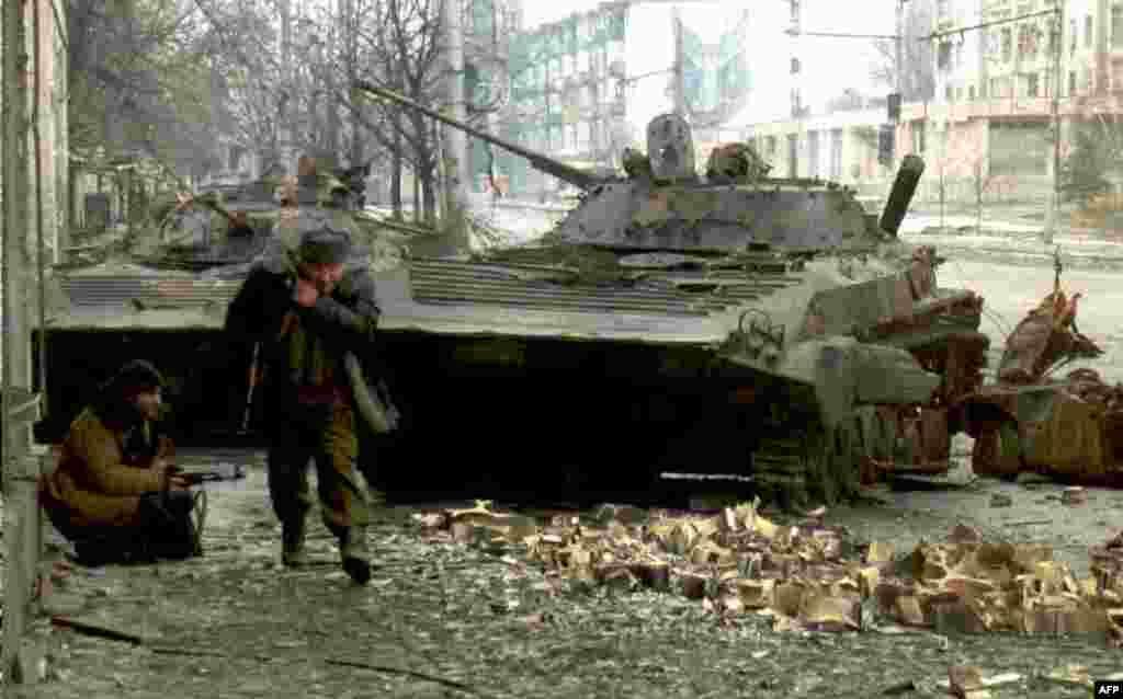 На фото – чеченские бойцы возле разрушенных русских танков, 10 января 1995 года