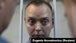 Ivan Safronov, a former journalist who works as an aide to the head of Russia's space agency Roskosmos, stands inside the defendants' cage at a July 7, 2020 court hearing in Moscow on charges of treason.