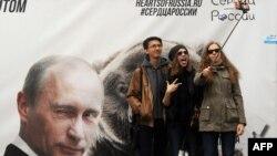 Молодые люди делают селфи на фоне баннера с президентом России Владимиром Путиным. Санкт-Петербург, 2 мая 2015