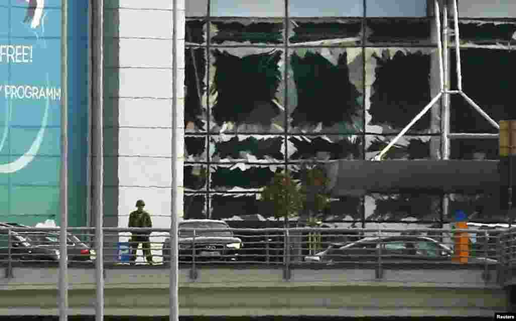 Солдат стоит у разбитых окон после взрывов в аэропорту Завентем около Брюсселя