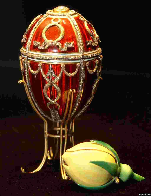 """""""Бутон розы"""" –первое яйцо, подаренное Николаем II своей жене царице Александре. Стрела Купидона выполнена из алмазов, а само яйцо покрыто красной эмалью. Внутри скрыт бутон розы – символ любви молодоженов. Спустя год после того, как этот подарок был преподнесен, сотни человек погибли в массовой давке на Ходынском поле –на торжествах по случаю восхождения на престол Николая II. По совету приближенных Николай II продолжил коронационные мероприятия, в то время как рядовые жители оплакивали погибших. Это была первая роковая ошибка царя."""