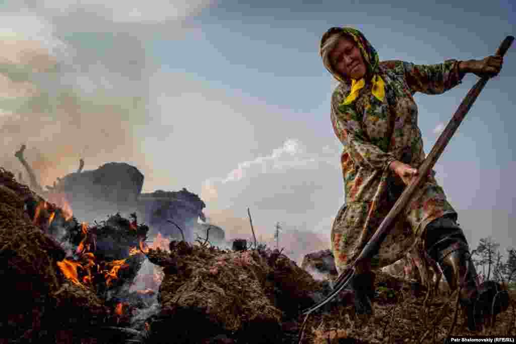 Любовь Мултанова не дает потухнуть горящему торфяному болоту. Исходящий от него дым защищает оленей от надоедливых мух