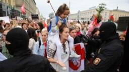 A woman carrying a girl confronts riot police during a women's march in Minsk against election fraud and police violence on August 29, 2020.