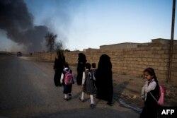 Жительницы освобожденного Мосула идут вдоль дороги. Перед выходом из Мосула члены ИГИЛ поджигали нефтяные разливы, чтобы затруднить операцию коалиции по освобождению