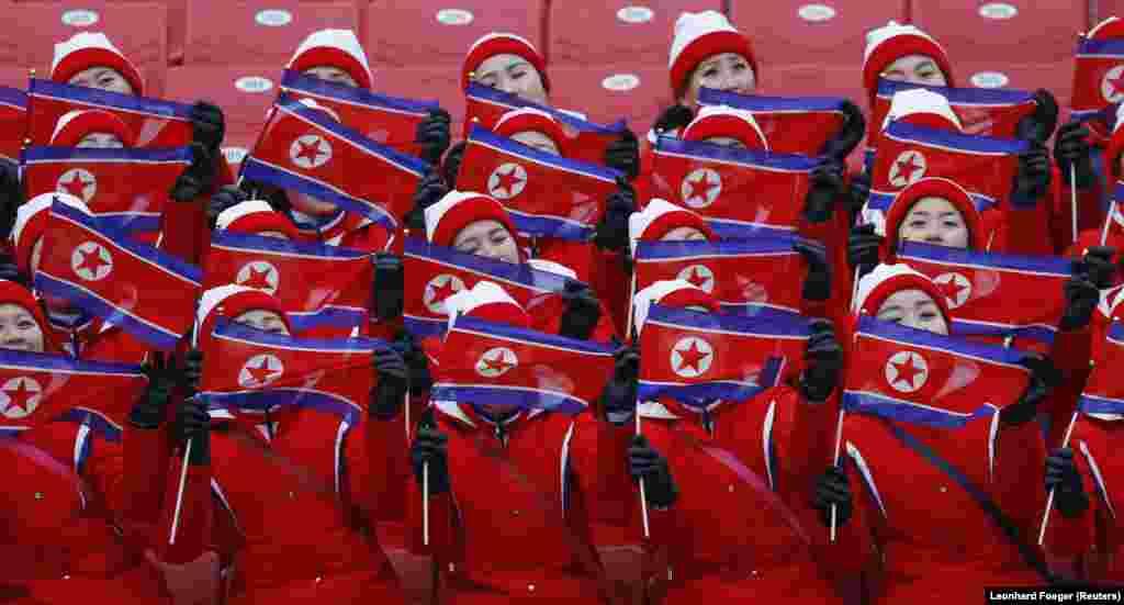 Девушки держат флаги КНДР на соревнованиях по горнолыжному спорту среди женщин в слаломе. 14 февраля 2018