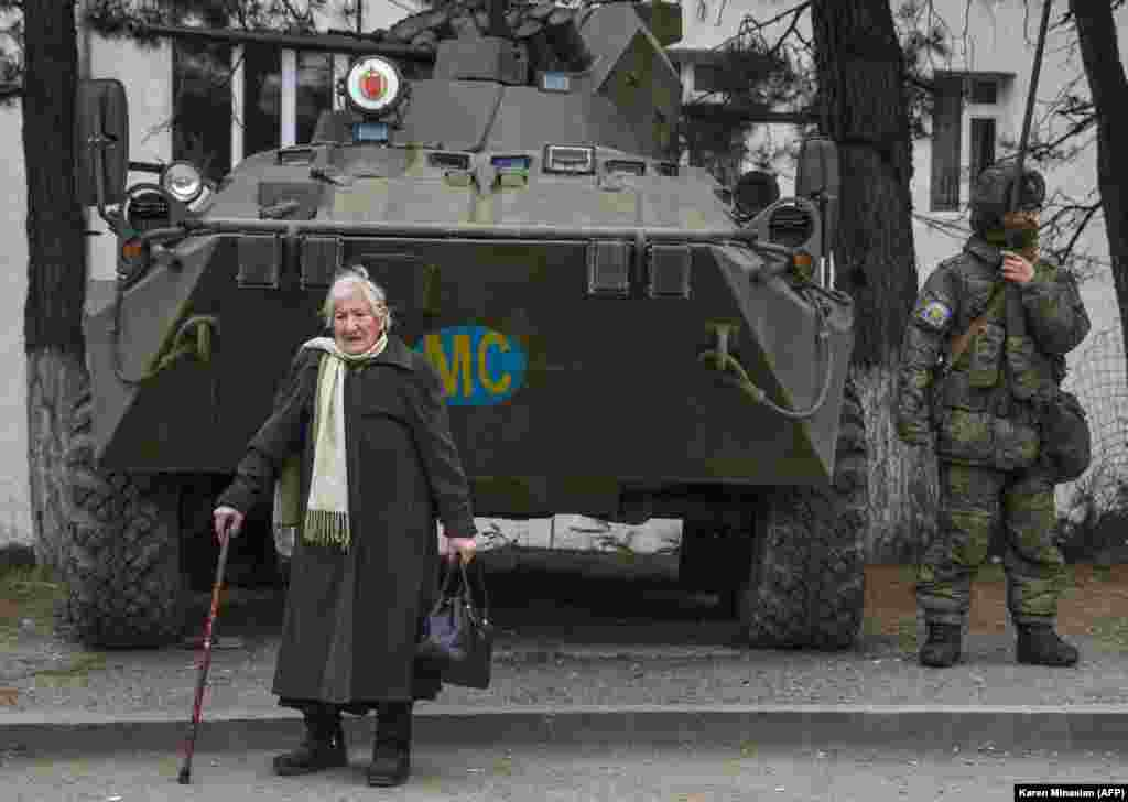 Five days before the arrival of Azerbaijani troops on December 1, 2020, Margarita Khanaghian, 81, walks past an armored personnel carrier for Russian peacekeepers in the town of Lachin (Berdzor). How many of the town's ethnic Armenian residents opted to stay despite the town's return to Azerbaijani control is unknown.