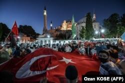 Люди возле Святой Софии в Турции скандируют лозунги и размахивают государственным флагом, 10 июля 2020 года. Фото: AFP