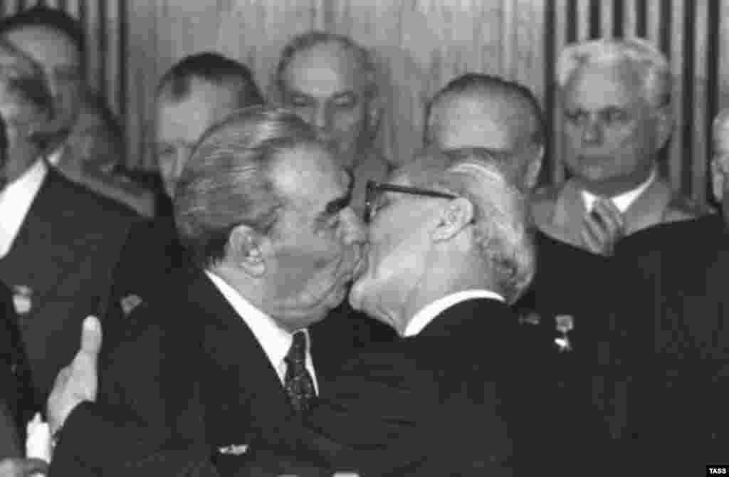 """Знаменитый поцелуй генерального секретаря КПСС Леонида Брежнева и лидера ГДР Эриха Хонеккера в 1979 году, который превратился в картину Дмитрия Врубеля на Берлинской стене под названием """"Господи, помоги мне выжить среди этой смертной любви"""""""