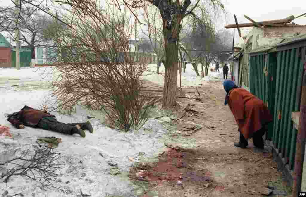 Местная жительница выходит из своего дома. Напротив дома лежит труп. Российские войска обстреливают Грозный тысячами артиллерийских снарядов.