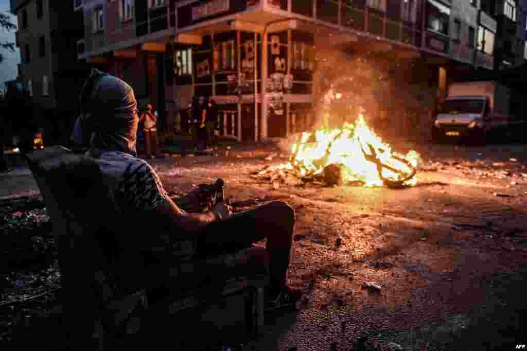 На фото - протестант сидящий напротив костра за баррикадами 26 июля