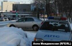 Баннер с Путиным (на заднем плане, за деревьями) и охраняющий его патруль ДПС