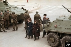 Civilians in Baku walk between a pair of Soviet tanks on January 28, 1990.