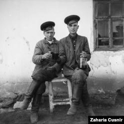Двое жителей деревни позируют с вином