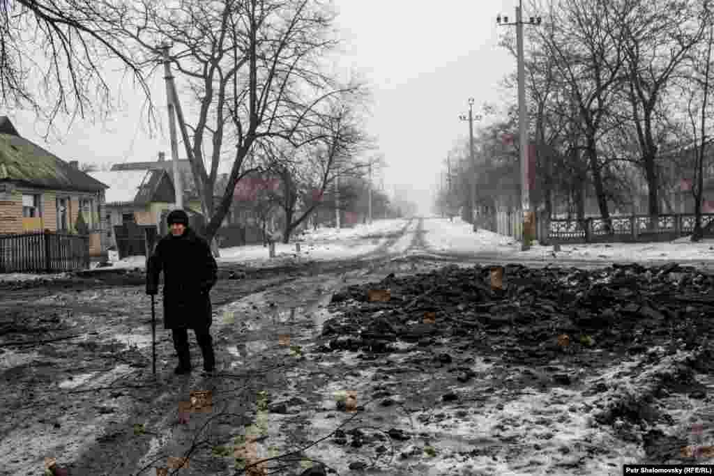 Валентина Павловна - жительница Дебальцево - обходит воронки, оставшиеся после обстрела. Она должна навестить свою больную тетю