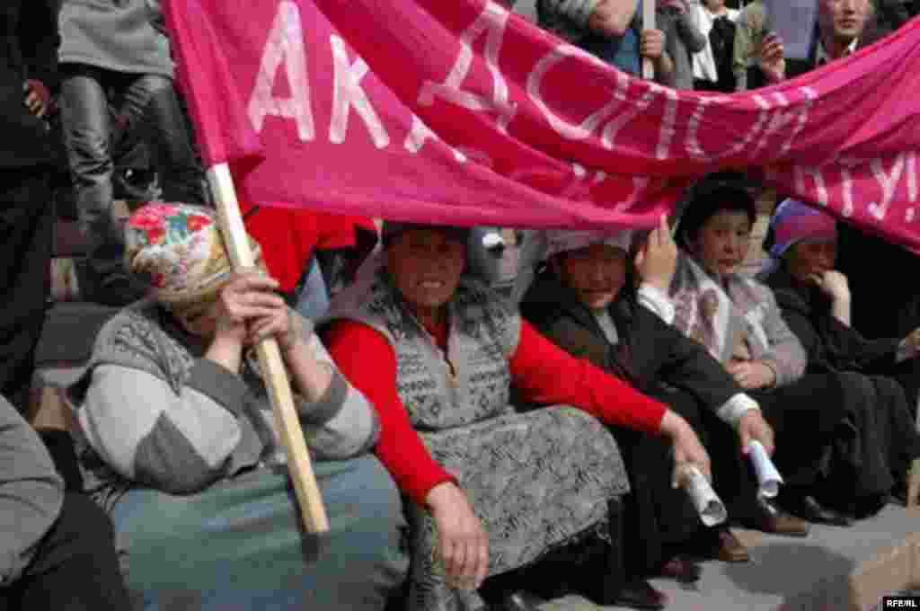 Участницы акции протеста держат плакат, призывающий Аскара Акаева уйти в отставку