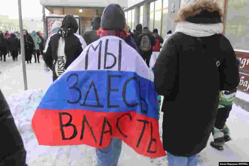 "A protester in Novosibirsk wears a Russian flag with the slogan ""We're in charge here."""