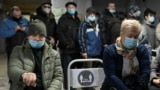 RUSSIA - People wearing protective face masks, used as a preventive measure against the spread of the coronavirus disease (COVID-19), wait in a queue near a reception desk at a local clinic in Omsk, Russia November 9, 2020