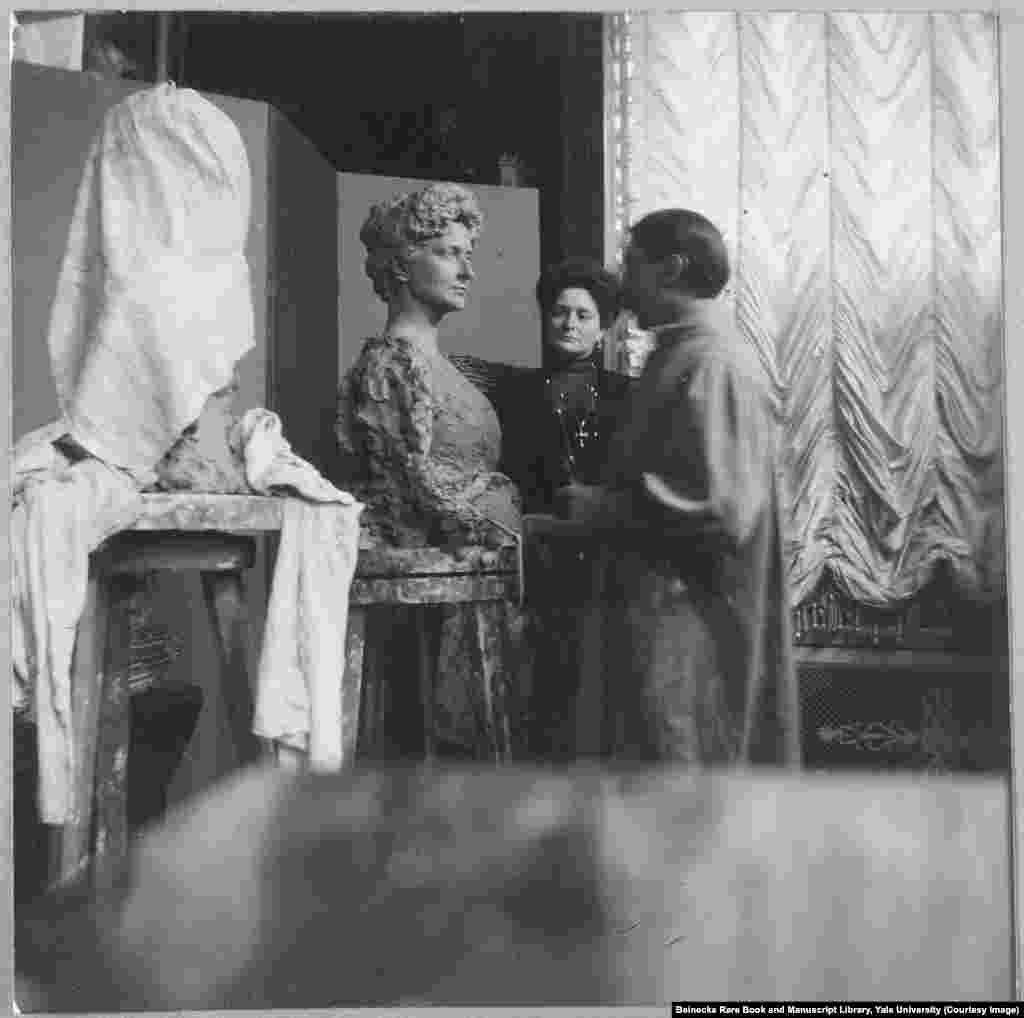 Императрица Александра рассматривает скульптуру из глины, напоминающую ее образ. За три года до революции, когда Россия вступила в Первую мировую войну и оказалась противницей Германии, к императрице, урожденной принцессеВиктории Алисе Елене Луизе БеатрисеГессен-Дармштадтской, в российском обществе стали относиться с подозрением и ненавистью, некоторые считали ее немецкой шпионкой