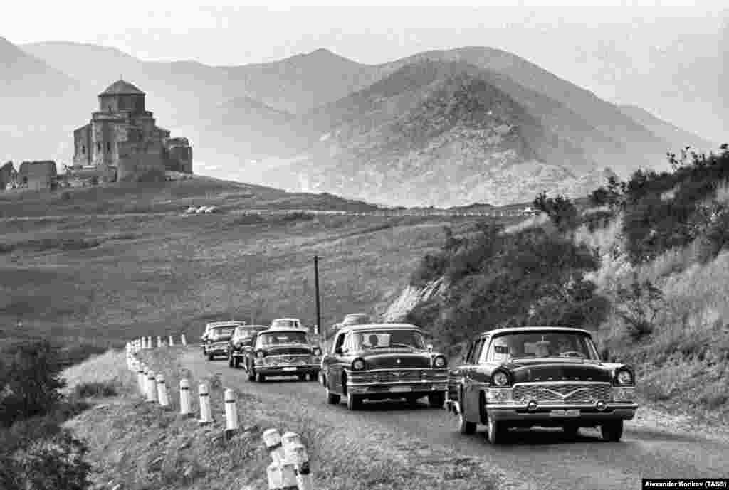 """Кортеж советских автомобилей марки """"Чайка"""" едет по дороге около Тбилиси. """"Чайка"""" была одним из нескольких советских автомобилей, которые в большей степени скопировали с западных моделей"""