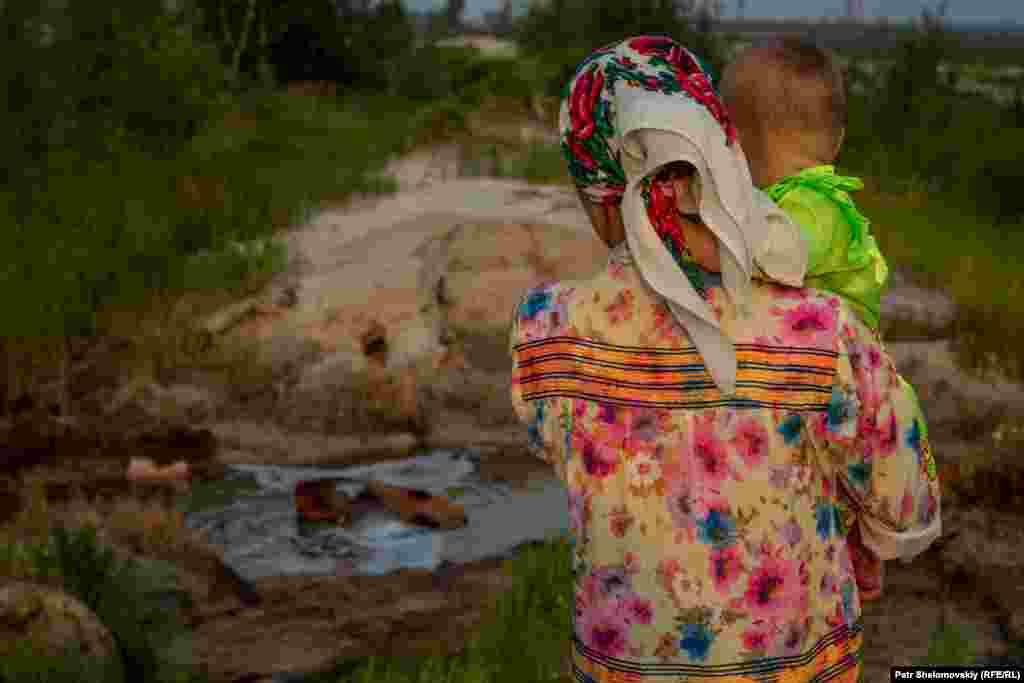 Фая смотрит на загрязненную воду, вытекающую из поврежденной бурением земли